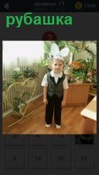 На полу в детском саду стоит мальчик в рубашке и шапочке с ушками