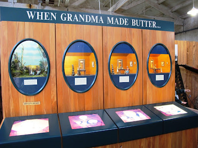 Display of model scenes depicting the four stages of making butter.