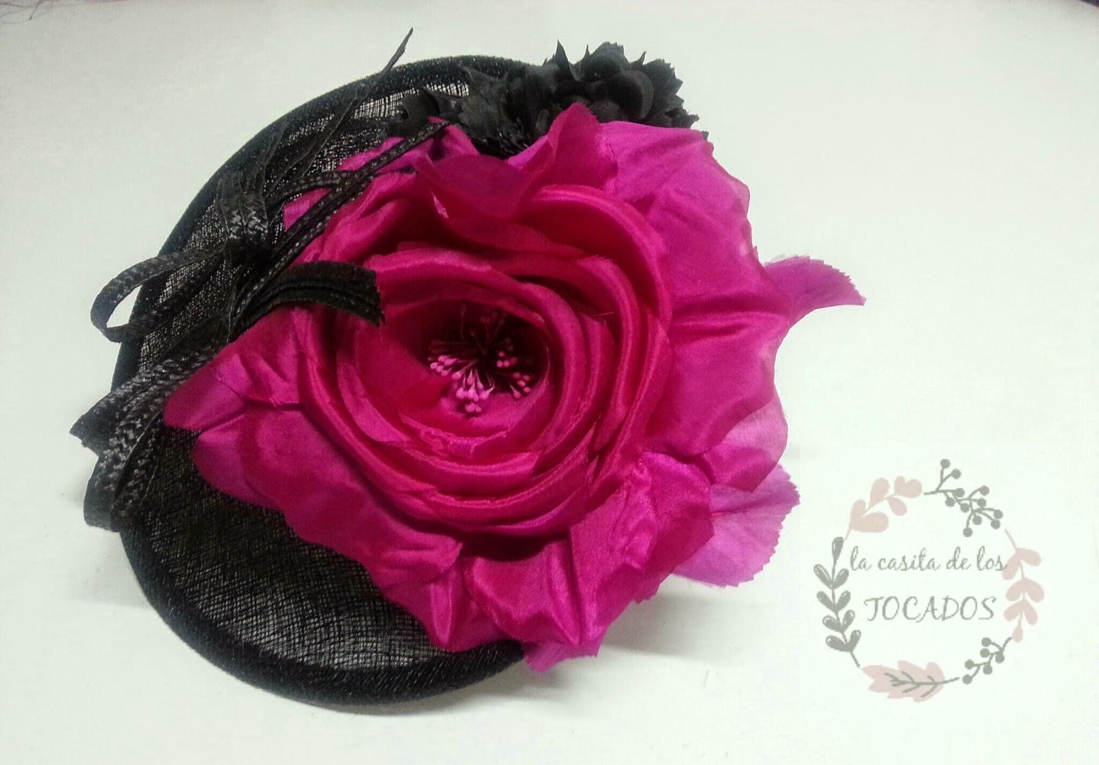 tocado fucsia y negro con base redonda invertida y dos flores una negra y otra fucsia