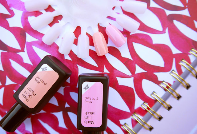 bottles of peach and pink nail polishes next to a white nail wheel showing swatches of both