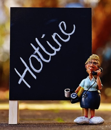 Woman Figurine on the Phone, with HOTLINE spelled out on a chalkboard behind her