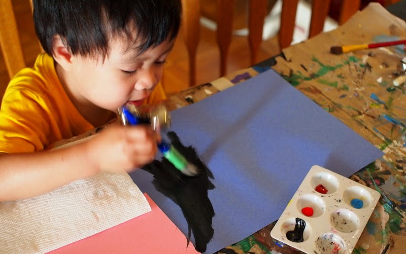boy painting with paint brushes and bells