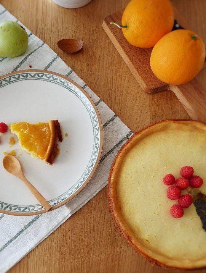 ración de tarta de queso con mermelada de naranja dulce y frambuesas