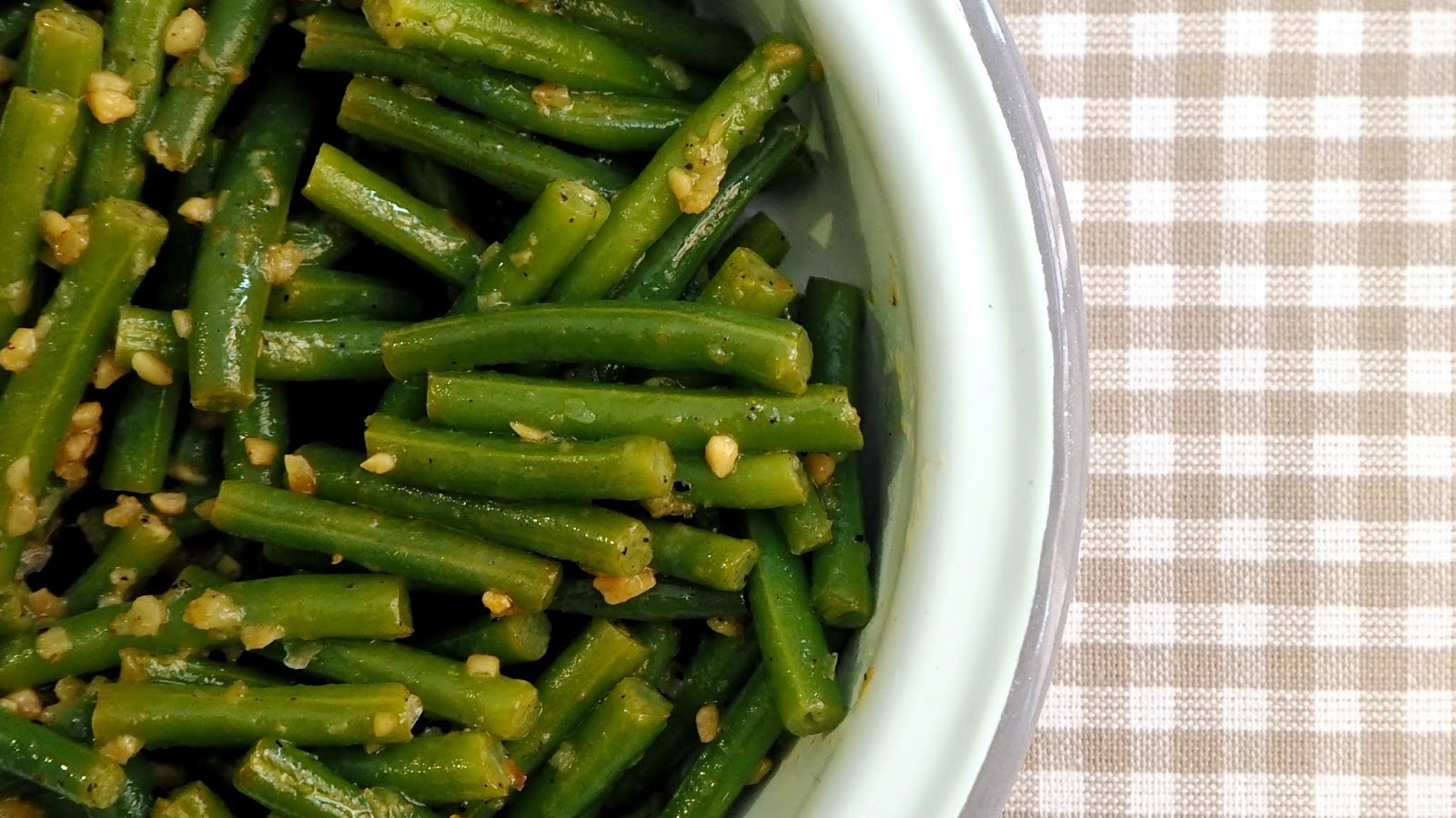 Bowl of green beans with garlic and lime on a tan checkered placemat