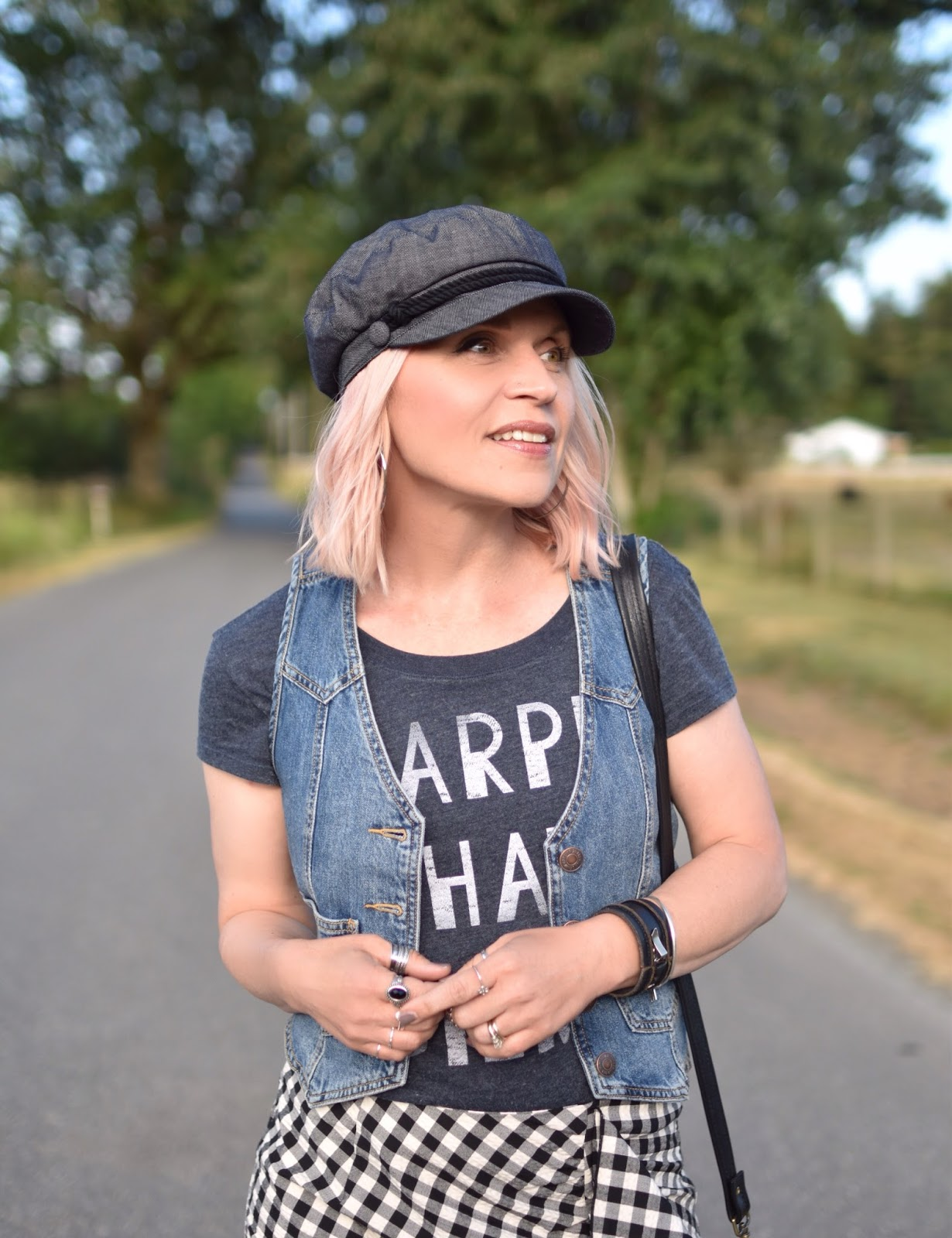 Monika Faulkner personal style inspiration - ruffled gingham skirt, graphic tee, denim vest, baker boy cap