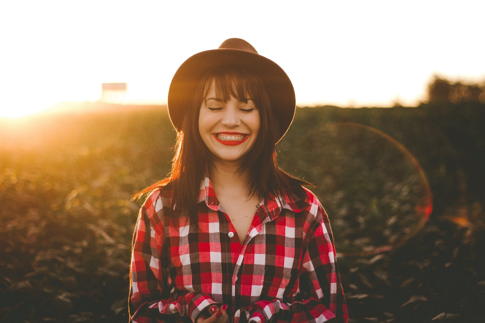 Living your values - smiling girl in a brown hat on a hillside at sunset