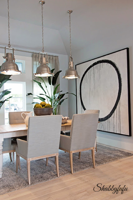A modern style painting of a giant black circle hangs on the wall in the dining room of the HGTV Dream Home 2016.