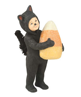 catnip by bethany lowe, child dressed in a black cat costume for Halloween holds a large candy corn piece