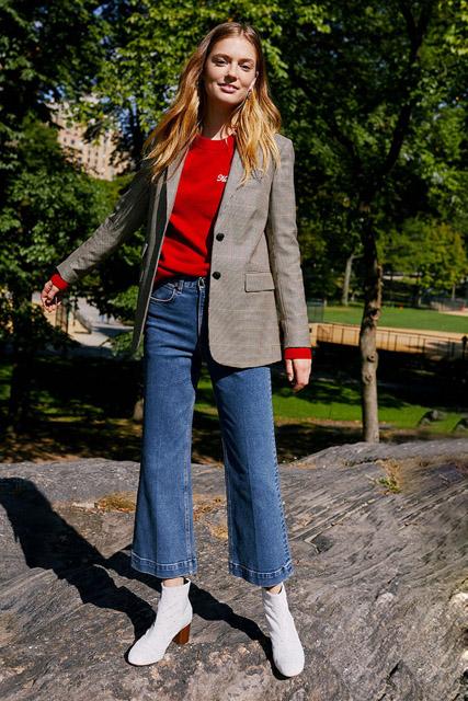 Девушка в жакете прямого кроя и красном свитере и джинсах клеш