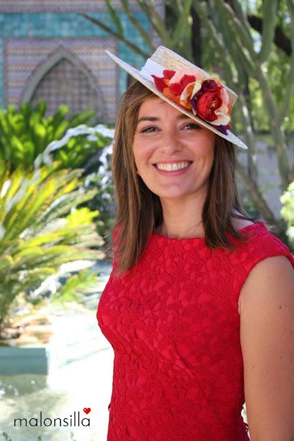 Invitada a boda con el pelo suelto, vestido rojo de encaje y canotier de copa baja con flores en rojo y naranja de marca malonsilla