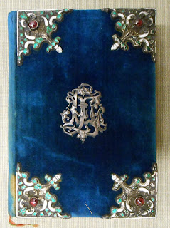 A blue velvet cover with worked metal elements.