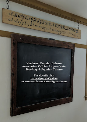An old school classroom and chalkboard with the conference info on it.
