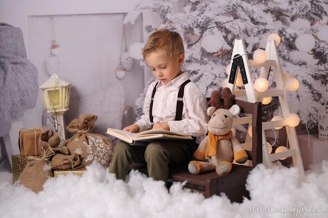 chłopiec w scenerii zimowej czyta reniferkowi bajkę i pozuje na sesji rodzinnej świątecznej