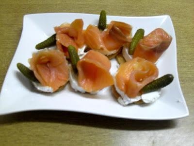 Tostadita de queso crema y rosa de salmón ahumado con pepinillos.