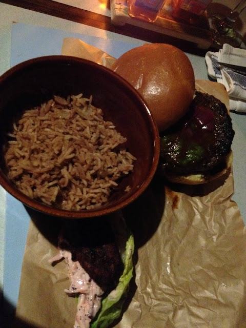 burger and bowl of rice on paper on a blue painted board