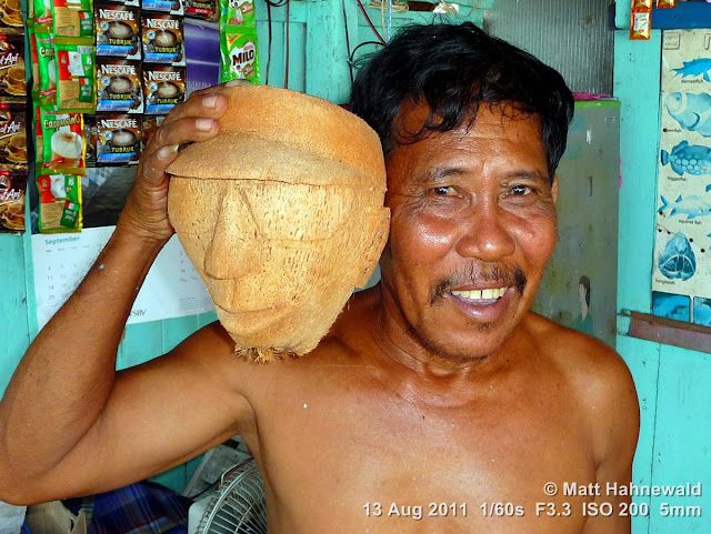 people, street portrait, local artist, coconut art, hand-carved coconut head, carving coconut heads, Indonesia, Central Sulawesi, Tanjung Karang, Facing the World, © Matt Hahnewald