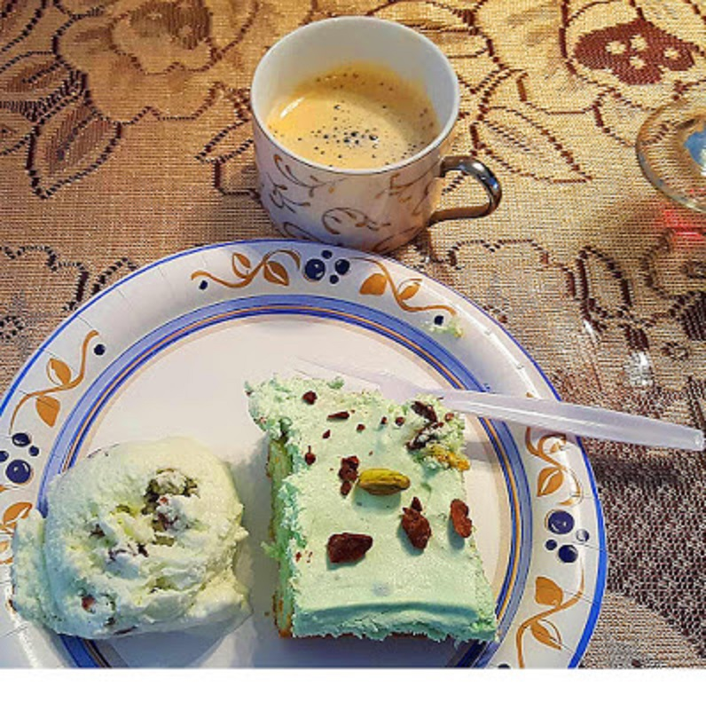 this is a sliced piece pistachio cake and a scoop of pistachip ice cream with a cup espressso in the backroud using a cake mix and pudding in the mixture with a pistachio whipped cream and garnished with pistachios and shaved chocolate
