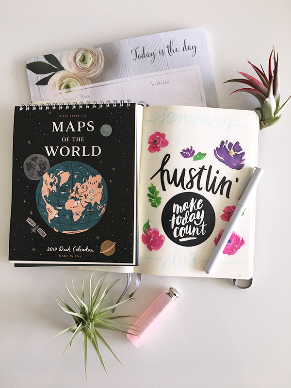 Flatlay featuring 2019 Rifle Paper Co. Maps of the World desktop calendar, bullet journal, Indigo notepad, Dior Addict Lip Glow, air plants