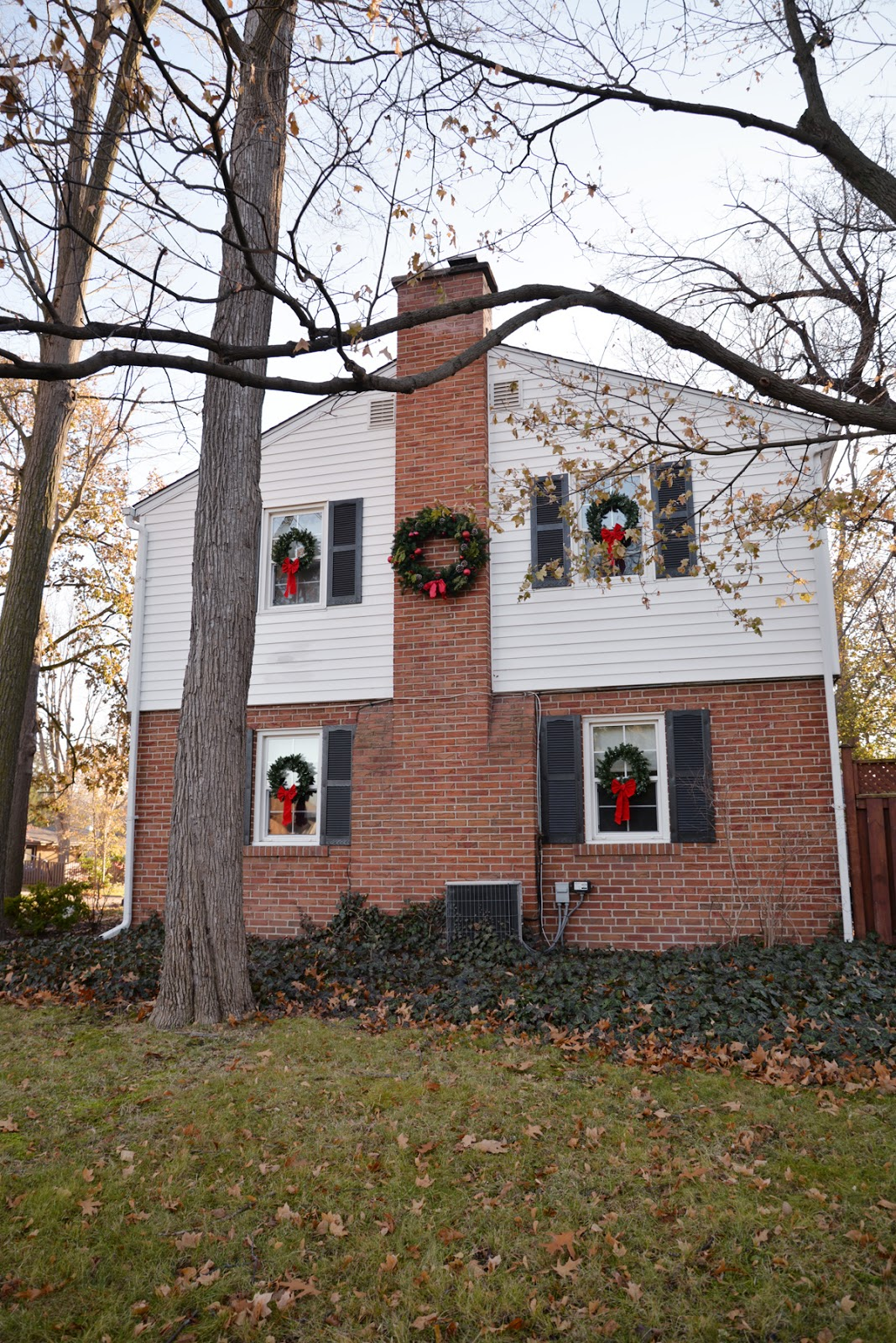 classic christmas decorations, colonial house with wreaths on windows, wreaths on exterior windows, wreath on chimney, large exterior wreath