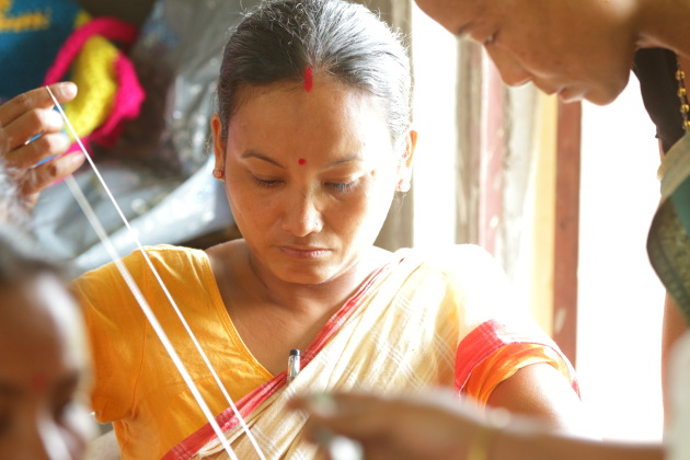 Mishing tribal woman learning the art of weaving at Panbari, Assam, India