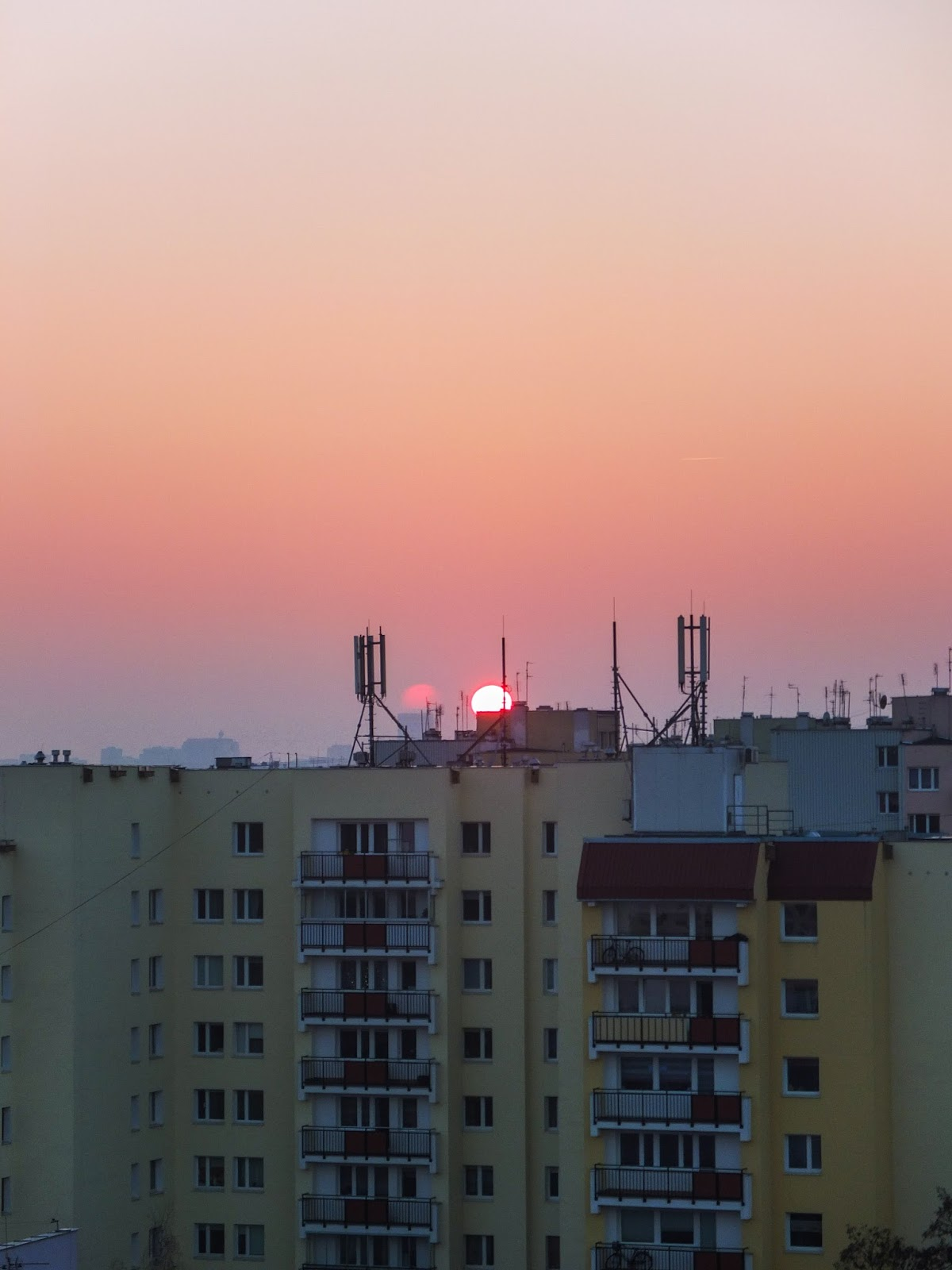 Sun setting over apartment buildings in Warsaw in the winter.