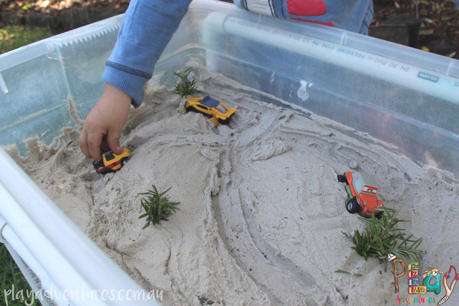 A child's hand driving a toy car through pretend sand dunes