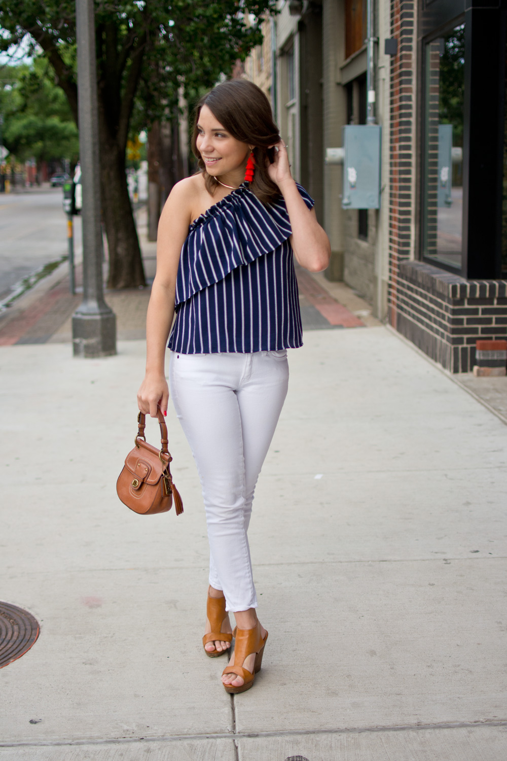 Americana Inspired outfit idea featuring white skinny jeans, a navy one shoulder top, and red tassel Baublebar earrings.