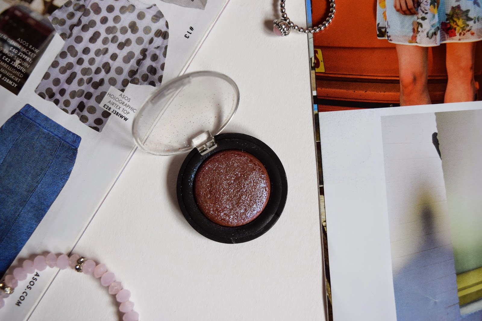 PINK EYESHADOW SINGLE LYING FLAT SURROUNDED BY MAGAZINES AND JEWELRY