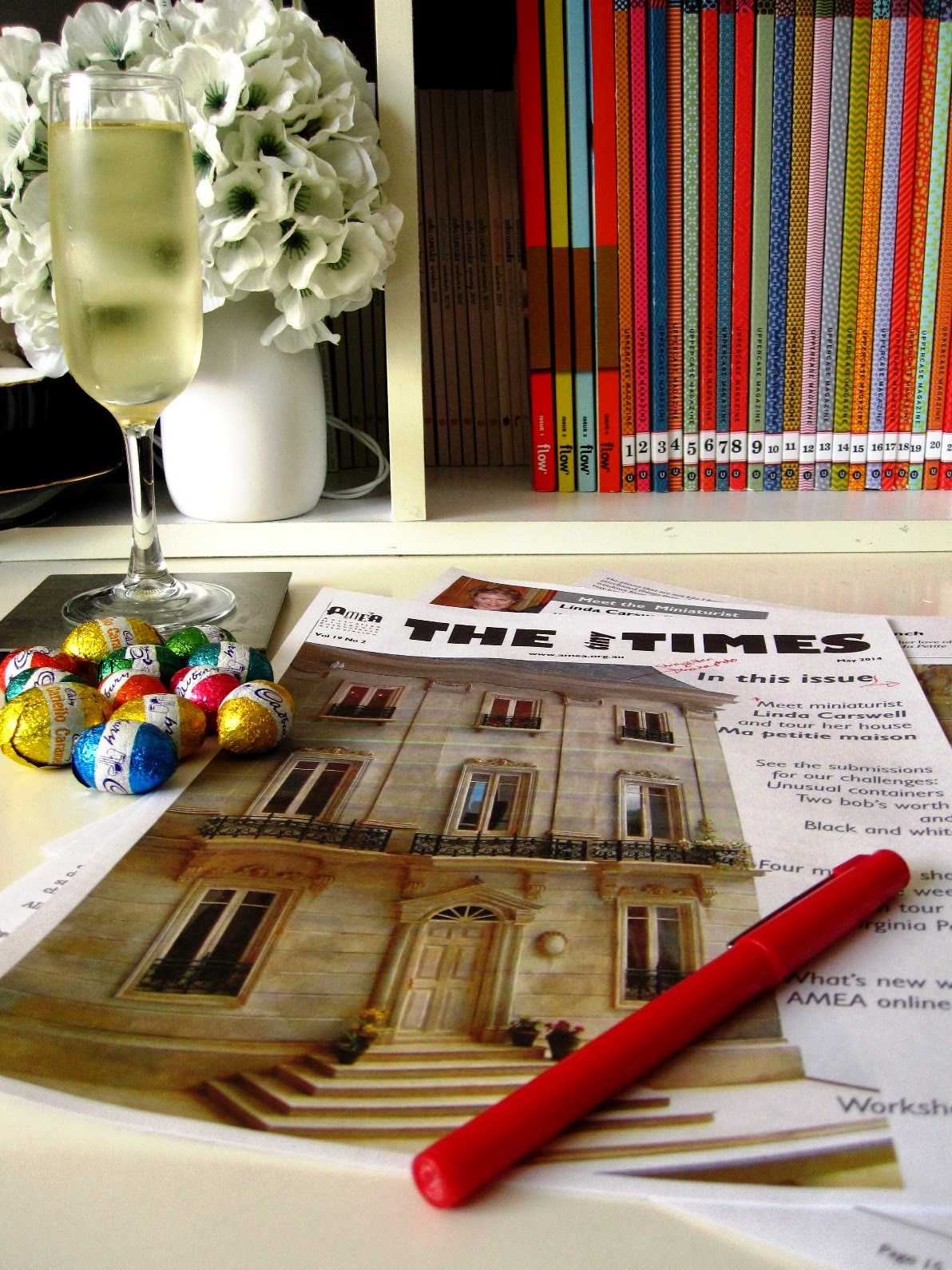 Printed out proofs of The tiny Times magazine on a desk, along with red pen, glass of sparkling wine and pile of small easter eggs.