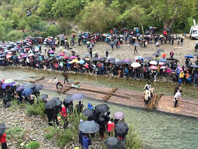 Spectators with umbrellas line the river