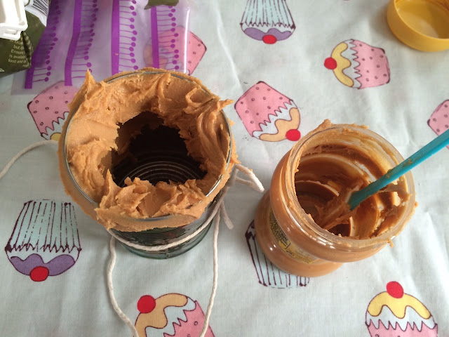 The opening of the can covered in peanut butter, inside and out