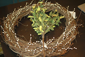 Add white berries and greenery to grapevine wreath