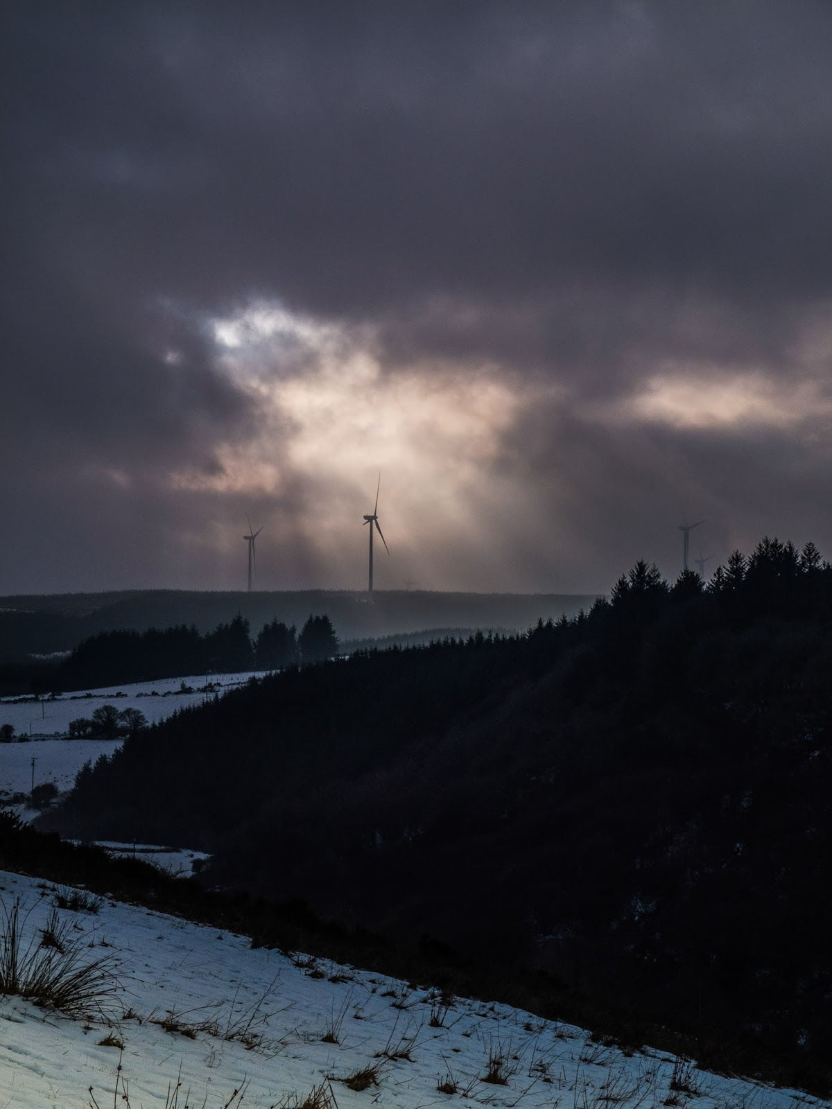Sun casting rays through dark clouds on wind turbines in the mountains.