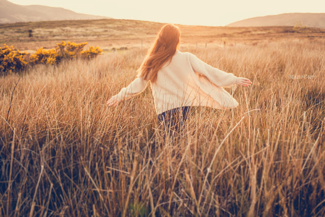Woman with long hair dancing in a field at golden hour