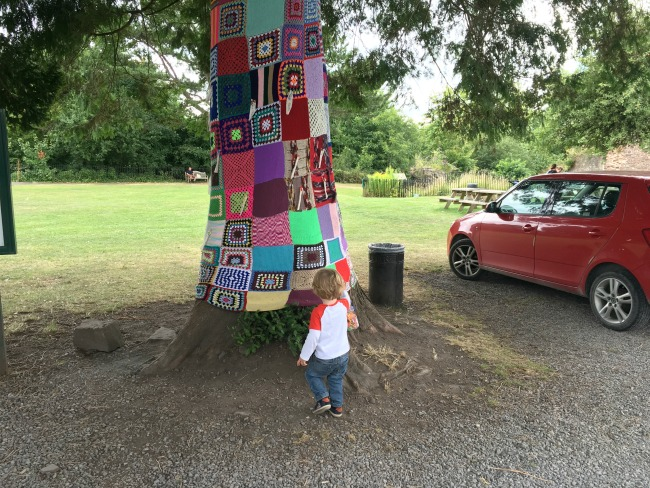 tree-wrapped-in-woollen-knitted-squares-and-toddler-and-parked-car