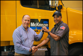 McKenzie Tank Lines president and CEO Jim Shaeffer presents 2017 Driver of the Year Antonio Cruz with the keys to his assigned new VNL 740.