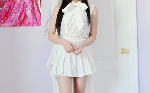 Details on the white dramatic ruffle high-low sleeveless gridded self-tie blouse from Twist X Turn, modeled with a pleated white tennis skirt from American Apparel for an all-white monochromatic look.