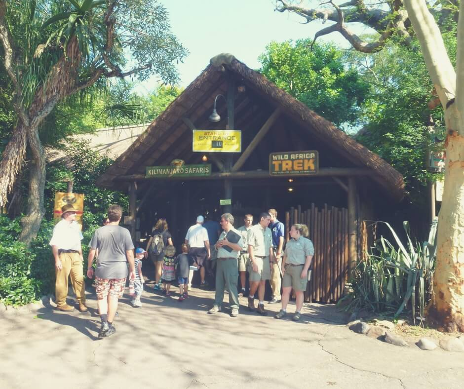 "A photo taken outside the entrance to Kilimanjaro Safaris at Animal Kingdom. A crowd of people are queuing outside the entrance. The sun is shining down on them, they are shaded by the surrounding trees. Image for ""How to get a much-needed rest at Animal Kingdom""."