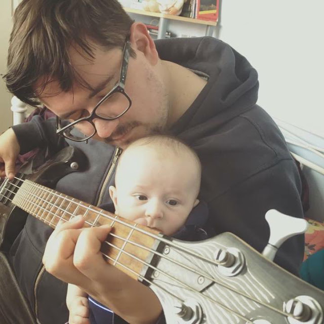 photo of father and baby boy with electric guitar