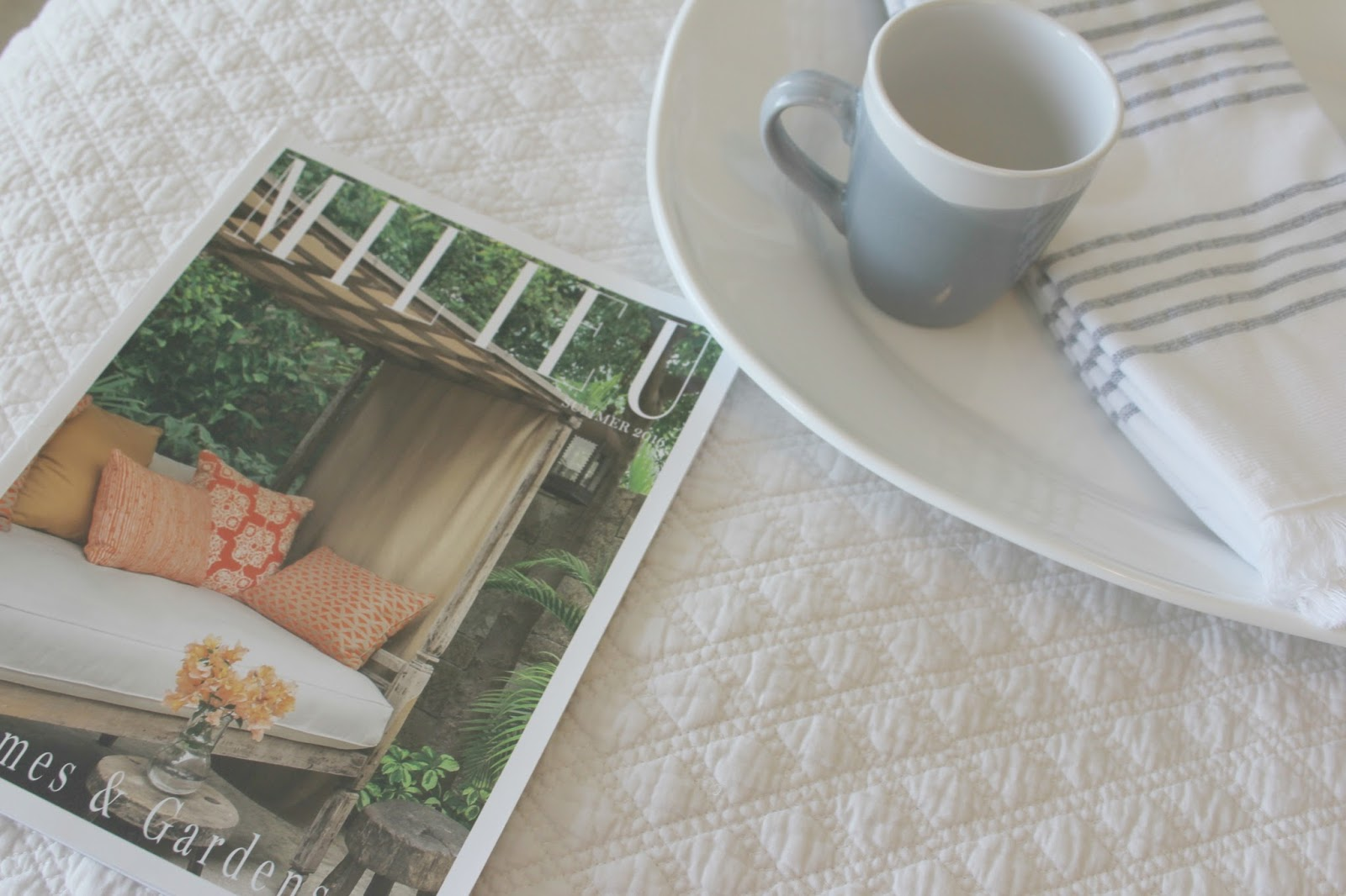 Milieu magazine on quilted coverlet in cozy serene bedroom by Hello Lovely Studio
