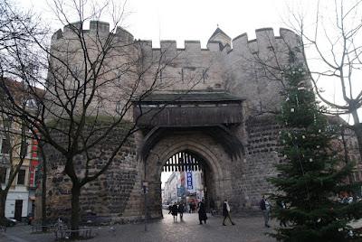 Ein burgartiges Gebäude mit zwei mächtigen Türmen rechts und links. In der Mitte ein hohes Durchgangsportal in Bogenform, darüber ein hölzerner Balkon. Im Portal ein angedeutetes Falltor.