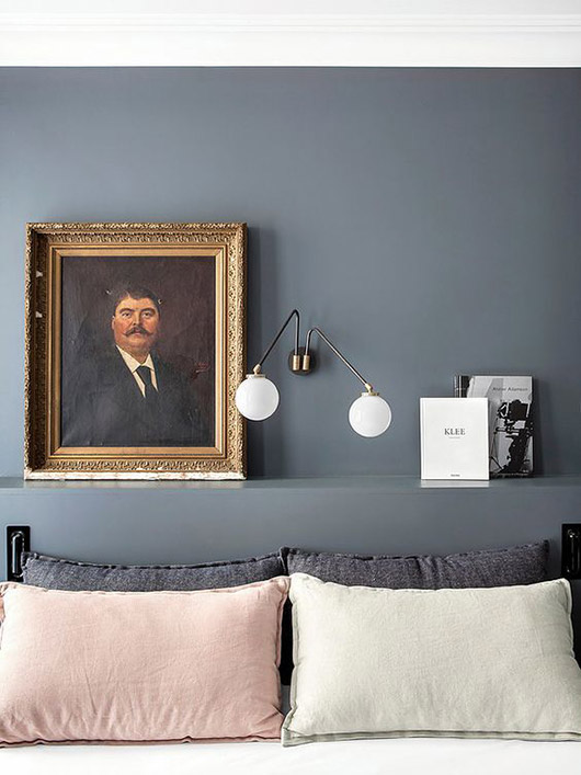 Grey wall and a golden framed portrait