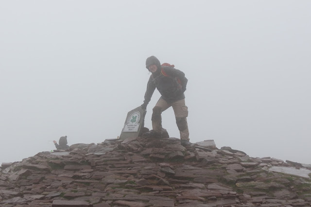 A picture of me, hat on and hood up, standing in the mist at the summit marker.