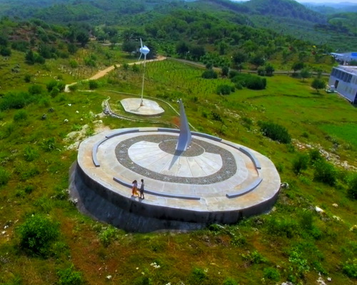 Tinuku.com Giant sundial overlooking Indian Ocean at cliff tops as Baron Technopark icons in hilly landscape Gunung Kidul
