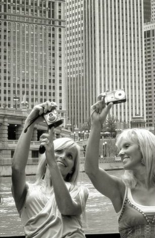 Two women taking photos of skyscrapers in Chicago