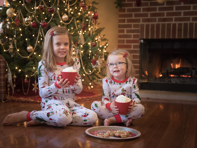 Christmas picture of two girls in Christmas PJs drinking hot chocolate