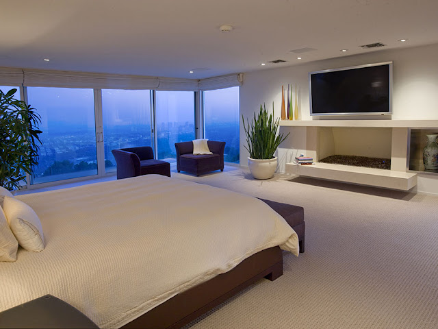 Picture of another large modern bedroom with large tv on the wall above the fireplace