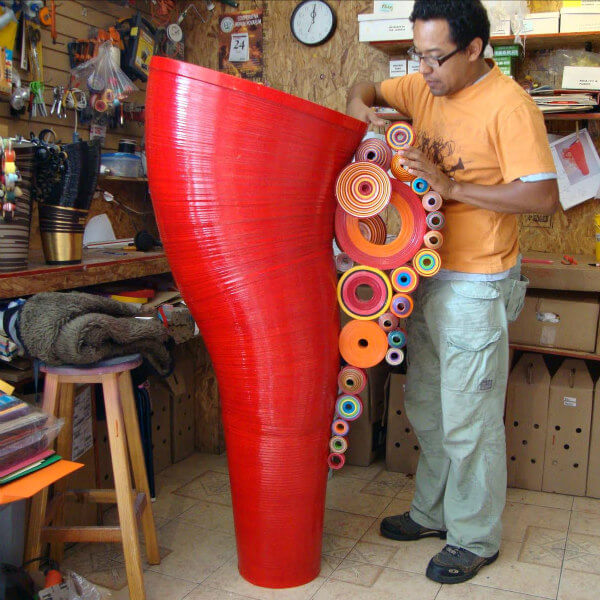 man creating large rolled paper art sculpture