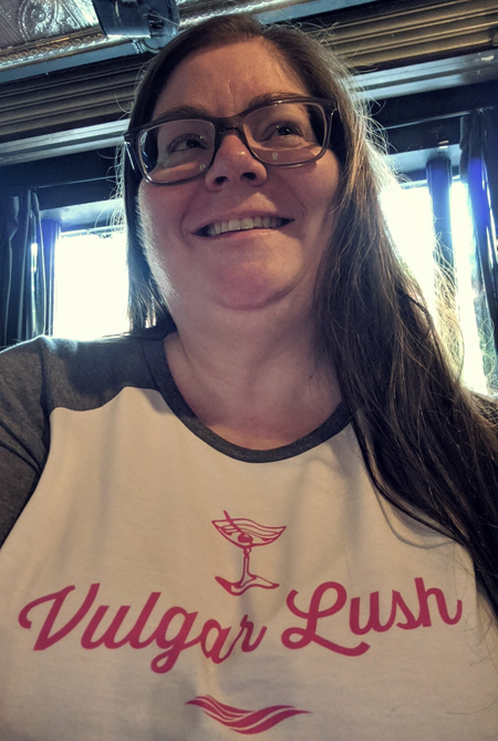 image of me in a bar, taken from my midsection looking upward; I am smiling with my hair down and wearing grey-framed glasses and a t-shirt that says 'Vulgar Lush'