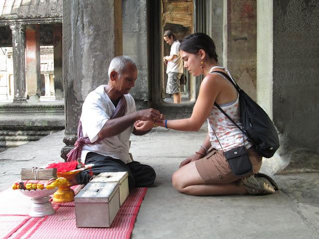 Monje camboyano diciendo una oración mientra pone una pulsera